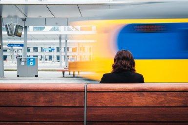Vrouw op bankje in station, trein rijdt voorbij