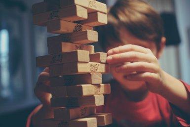 Kind speelt met blokken (het spel Jenga)