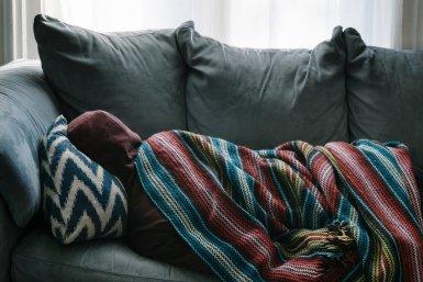 Ziek thuis op de bank onder een dekentje