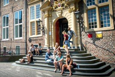 Studenten in de zomer op de trappen voor de ingang van Janskerkhof 3
