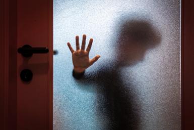 Kind achter een glazen deur.