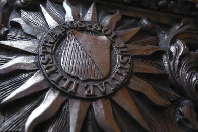 Historisch logo Universiteit Utrecht op houten bank
