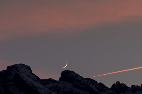 waxing moon crescent over mountains