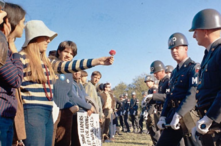 A demonstrator offers a flower to a military policeman on guard at the Pentagon during an anti-Vietnam War demonstration, October 1967. Source: Wikimedia Commons