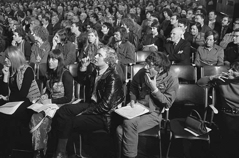 """Discussie in Krasnapolsky tussen """"De Notenkrakers"""" en het Concertgebouworkest (Amsterdam). Voorste rij Reinbert de Leeuw (rechts, met bril), links naast hem Peter Schat, 22 april 1970. Bron: Wikimedia/Bert Verhoeff (ANEFO)"""