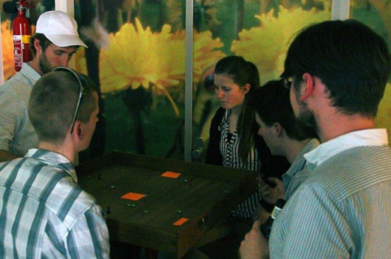 Bezoekers spelen een bordspelversie van Asteroids