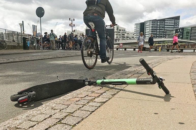 Elektrische scooter gedaald en verlaten op een fiets Lane en bestrating. Probleem met E-scooters rommelige straten van de stad.