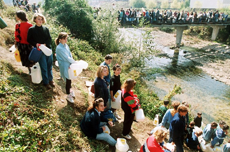 Residents of Sarajevo stand in line to get water, 1992. Source: Wikimedia Commons/Mikhail Evstafiev