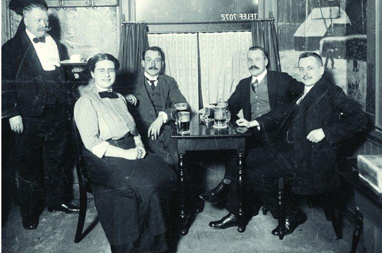 Johanna Westerdijk (zittend links) in gezelschap van vier mannen aan een tafeltje in café Eik en Linde te Amsterdam. (c) Schuitvlot, Nico - Collectie IAV - Atria, kennisinstituut voor emancipatie en vrouwengeschiedenis.