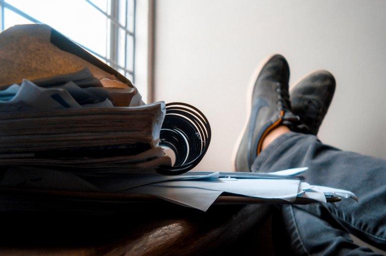 Bureau met stapels papier en voeten erop