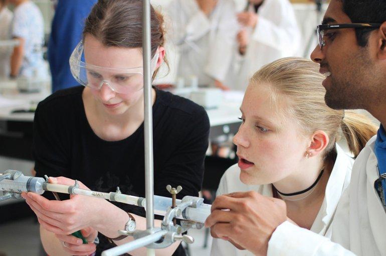 Studenten begeleiden scholieren tijdens scheikundepracticum