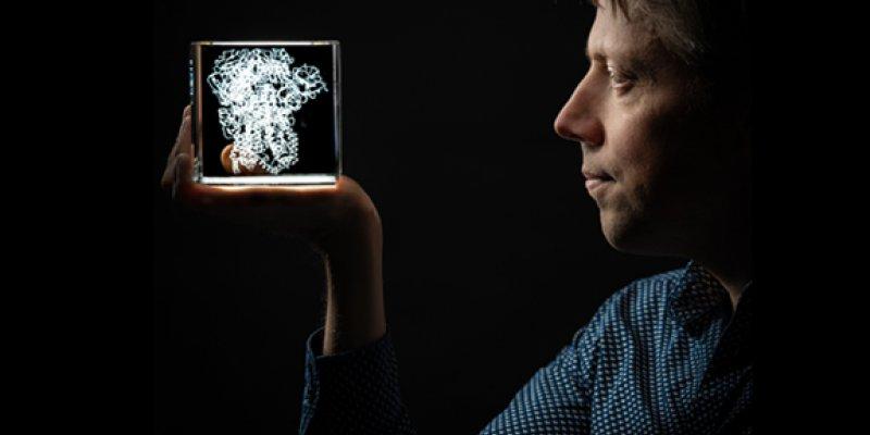 Onderzoeker Berend Jan Bosch kijkt in een model van een coronavirus dat in een doorzichtige kubus zit
