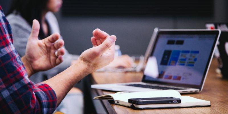 Man legt iets uit met handen, voor laptop, schrift en telefoon