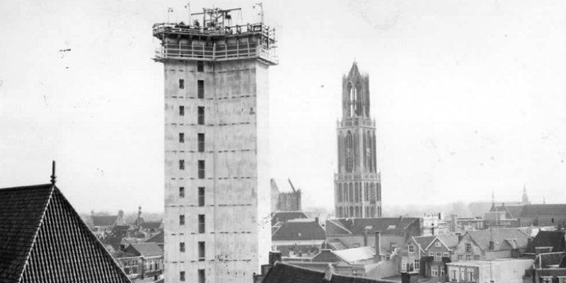 Gezicht op de in aanbouw zijnde Neudeflat (Vinkenburgstraat 26) te Utrecht, uit het noorden. Op de achtergrond de Domtoren (1961).  © Het Utrechts Archief