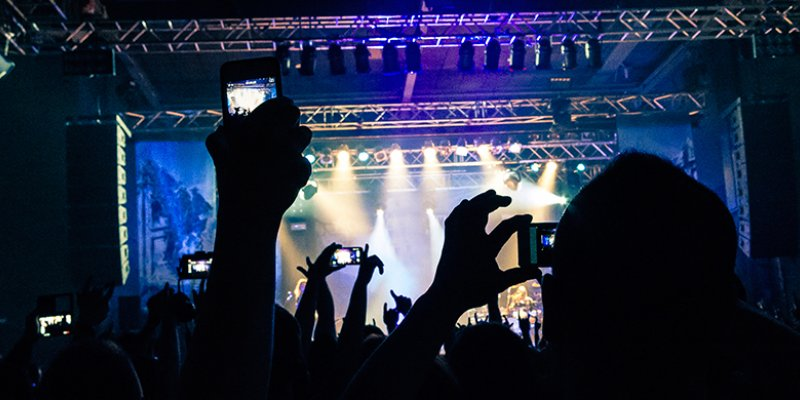 Silhouette of hands holding a mobile phone and taking a video of a rock concert © iStockphoto.com/jericho667